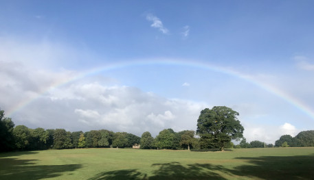 A park in the sunshine with a rainbow stretching over the whole sky