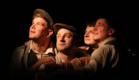 Shot from the chest up, four men, all in 1940s flannel shirts and waistcoats, and two in flat caps, stand in a group, holding or resting their arms on each other. They look up to the top left, where light is entering the dark shot.