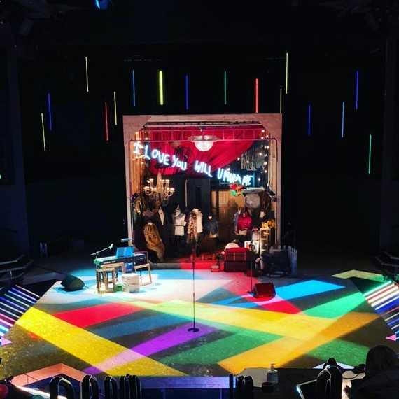 The stage for the quiz, props and costumes are displayed. The stage is filled with cross lights of bright colours