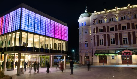 On the left, the Crucible lit up at night in purple and pink. Customers swarm through the doors. The Lyceum on the right, up-lit.
