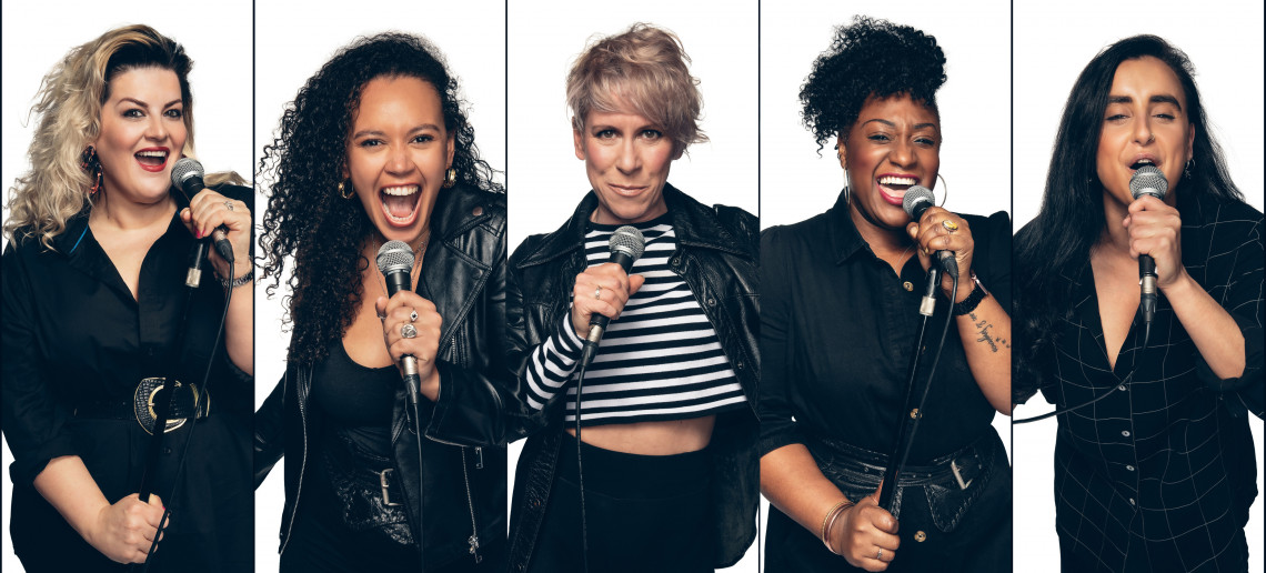 The cast of 5 women singing into their microphones