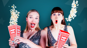Two woman facing straight ahead throwing popcorn in the air