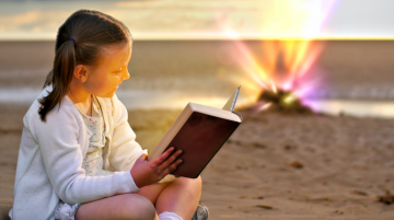Young girl reading a book on a beach