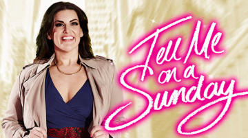 A woman is stood in front of a pale tan city scape. She is wearing a tan mac coat and smiling out, looking ahead. To the right is the title in neon pink: 'Tell Me On a Sunday'.