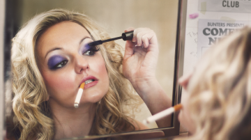 A young woman with dyed blonde hair and dark purple eyeshadow applies mascara in a mirror. A cigarette hangs from the edge of her mouth.