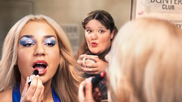 A woman looks into a mirror, applying lipstick. Another woman behind clutches a cup of tea, watching her friend apply makeup
