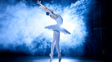 A ballerina in traditional white tutu stands en pointe, back arched, arms outstretched. From the left, fog pours in, through which a light shines from the very back.