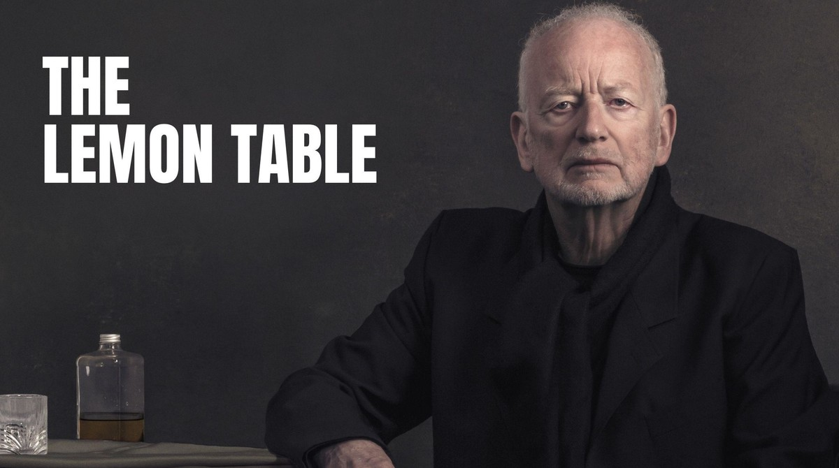"""An older man dressed all in black stares solemnly into the camera. Shot from the chest up, he seems to be sat at a table. Next to him rests an empty square glass bottle. Text reads """"The Lemon Table""""."""