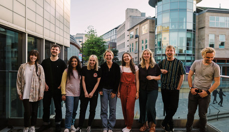 9 members of the Young Company standing together outside smiling and laughing