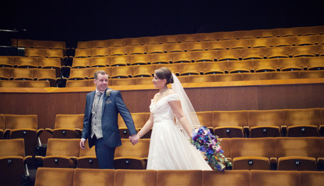 A bride and groom celebrate their wedding inside the Crucible Auditorium