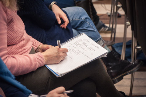 A staff member taking notes during a meeting