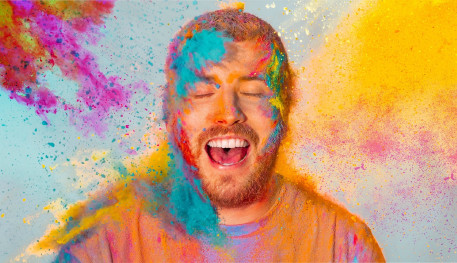 Man looking happy with powder paint being thrown at him