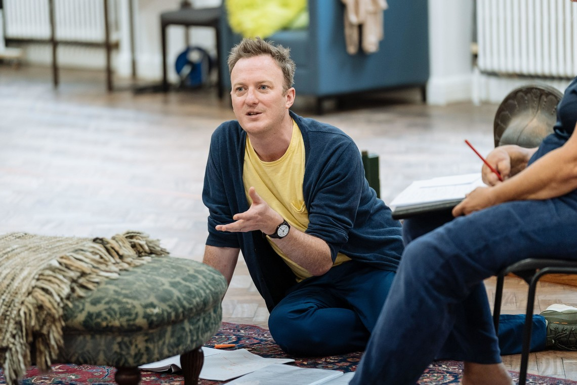 Paul, a white man with blonde hair, sits on a rehearsal room floor with props surrounding him. He is talking to an actor out of shot.