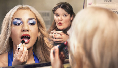 Two women reflected in the mirror in a 70s talent club dressing room. Julie on the left applies lipstick, Maureen on the right sips her tea.
