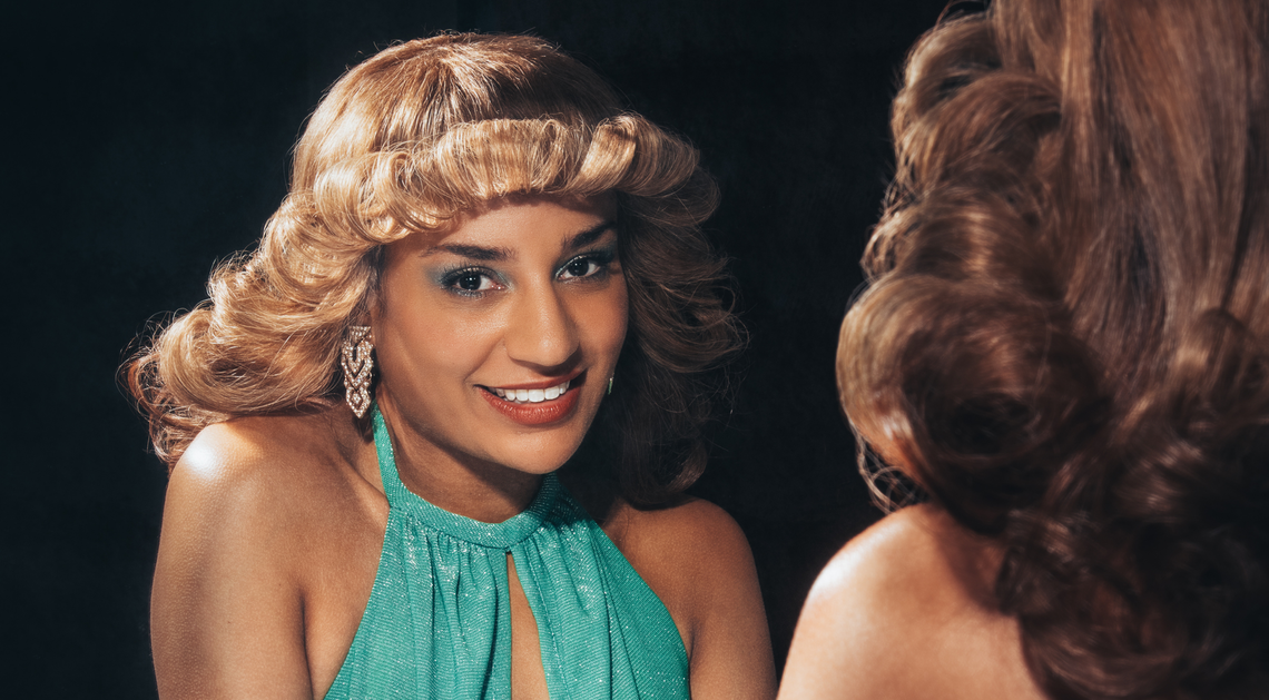 Lucie Shorthouse in character as Julie, smiles through the reflection of a mirror. She wears a sparkly green dress and has big 1970s hair