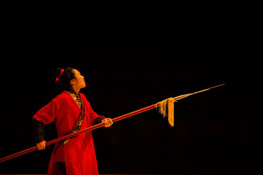 An actress is in a traditional Chinese war outfit. She is looking up, holding a spear at waist height, tilted upward.