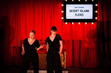Two female dancers pose mid-comedy dance routine. Both are wearing black jumpsuits and red lipstick. They are in front of a vibrant red curtain and a sign surrounded by lights that reads 'Desert Island Flicks'.