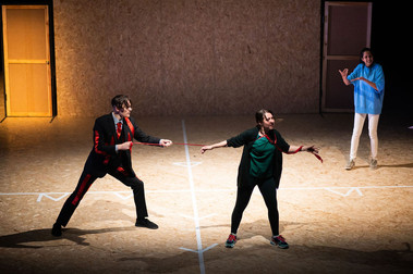 Three dancers stand on stage in everyday clothing. One is stage left, pulling away from another who stands stage right, holding them by a strip of red fabric tied to the first dancer's wrist. Another dancer looks on, moving towards them.