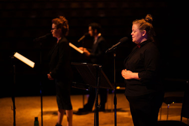 Three actors, two women and one man, stand in a horizontal line with microphone stands and music stands which hold scripts. The image is taken side-on: the first actor is in focus and the focus softens throughout the line. They are all dressed in black.
