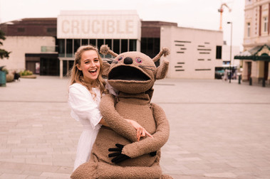 An actress stands on Tudor Square with the Crucible in view behind her. She is in costume in a white dress and is holding a large animalistic puppet, 'The Sandfairy'. She is smiling widely.