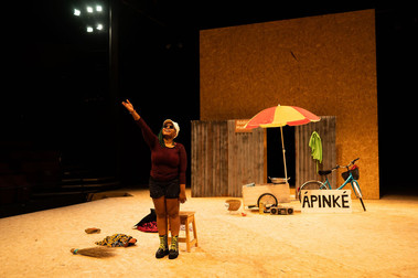 A smiling actress stands on stage in a long-sleeve t-shirt, shorts, laced up combat boots, and sunglasses. She is holding her arm aloft, pointing to something out of frame. Behind her is an assortment of props, including a bicycle, a sun parasol, and a sign bearing the character's name (Ápinké).