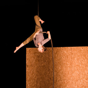 An aerial artist hangs from a rope from above. She is upside down, one leg wrapped around the rope, the other split, pointing toward the floor.