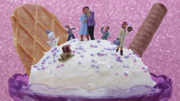 A snowy scene with small model people on an ice cream, a couple are surrounded by a snow man and kids chucking snow balls