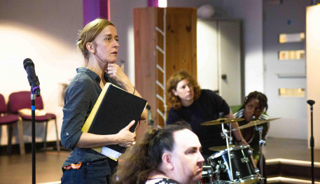 Lucy Ellinson playing Marie in Typical Girls in rehearsals. Four woman of varying age and ethnicity look concerned or interested. They are gathered around a drum kit and Lucy holds a clipboard.