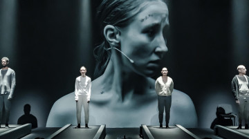4 actors stand at the back of a stage, facing out, parallel to each other. In front of each of them is a long conveyor belt. Behind them, projected onto the back is a large image of a woman in side profile.