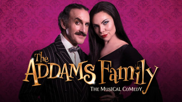 """A man and a woman stand close, facing the camera, heads tilted towards each other. Shot from the waist up, he is wearing a bold pinstripe suit and bowtie and has a bushy handlebar moustache. She is in a long-sleeve black dress with very long sleek black hair. They are both smirking. Text reads """"The Addams Family: The Musical Comedy""""."""