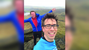 Dan and Boff, two middle age white men, stand atop a windy hill in the Peak District. One has his arms outstretched and they are both smiling.